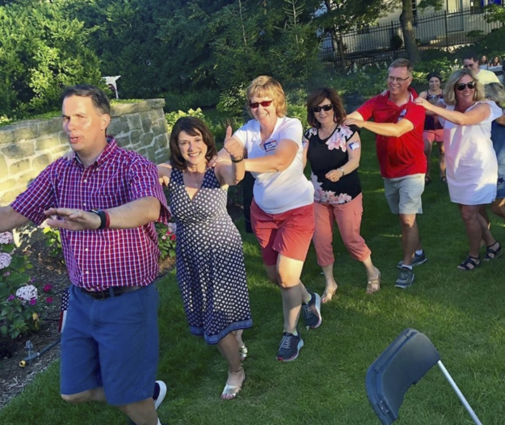In this Saturday, July 7, 2018, photo provided by the Leah for Senate campaign, Wisconsin state Sen. Leah Vukmir, a candidate for the U.S. Senate, gives a thumbs up while taking part in a conga line with Gov. Scott Walker, left, during a party at the executive residence in Madison, Wis. (Leah for Senate campaign via AP)