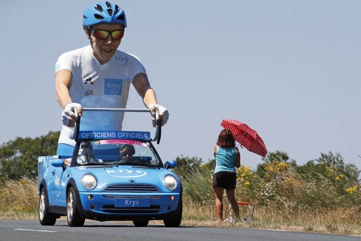 A sponsor vehicle passes a woman who shields herself from the sun as she waits for the team to pass during to the third stage of the Tour de France cycling race, a team time trial over 35.5 kilometers (22 miles) with start and finish in Cholet, France, Monday, July 9, 2018. (AP Photo/Christophe Ena)