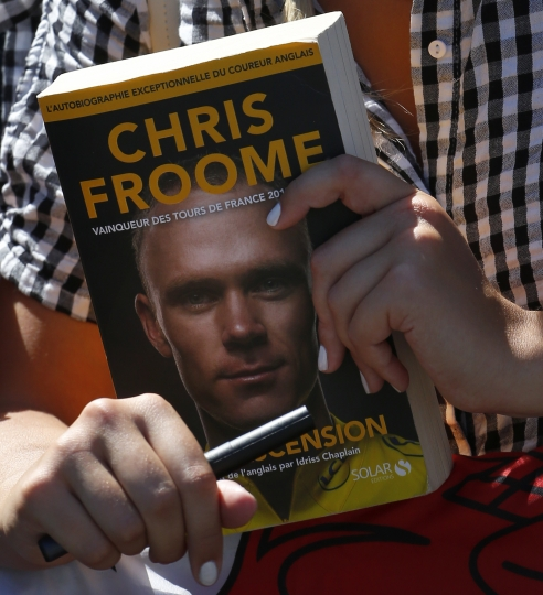 A woman waits for an autograph of Britain's Chris Froome prior to the third stage of the Tour de France cycling race, a team time trial over 35.5 kilometers (22 miles) with start and finish in Cholet, France, Monday, July 9, 2018. (AP Photo/Peter Dejong)