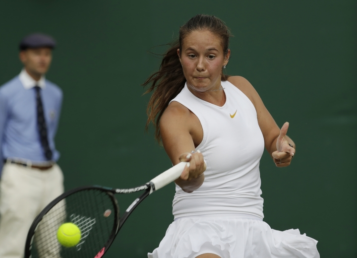 Daria Kasatkina of Russia plays a return to Alison Van Uytvanck of Belgium during their women's singles match on the seventh day at the Wimbledon Tennis Championships in London, Monday July 9, 2018. (AP Photo/Ben Curtis)