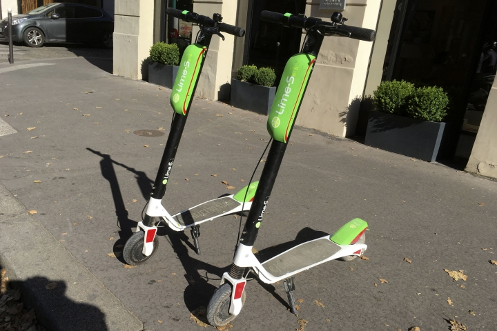 This July 3, 2018, photo shows scooters by Lime in Paris. Uber is getting into the scooter-rental business. The ride-hailing company said Monday, July 9, that it is investing in Lime, a startup based in San Mateo, California. (AP Photo/Michel Euler)