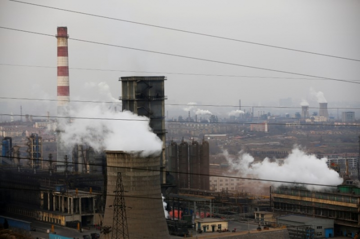 FILE PHOTO: Cooling towers emit steam and chimneys billow in an industrial zone in Wu'an, Hebei province, China, February 20, 2017. REUTERS/Thomas Peter