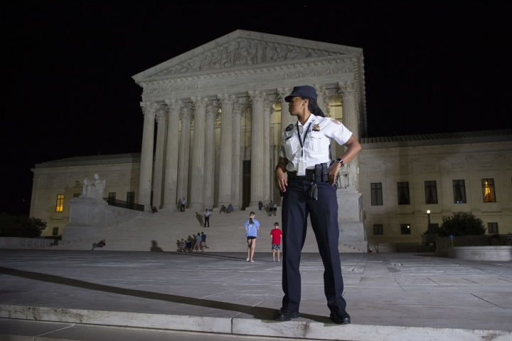 A Supreme Court Police officer stands watch as a protesters demonstrate in front of the Supreme Court in Washington, Monday, July 9, 2018, after President Donald Trump announced Judge Brett Kavanaugh as his Supreme Court nominee.. (AP Photo/Cliff Owen)
