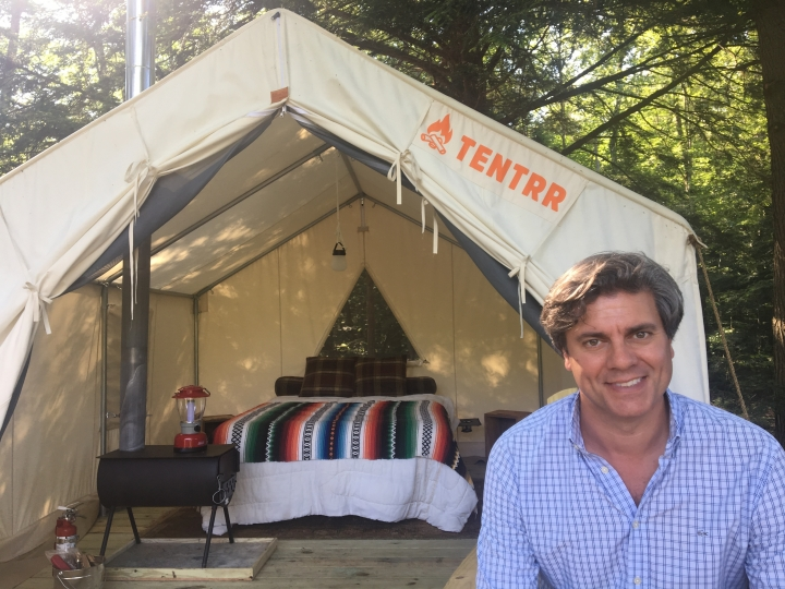 In this Friday, June 29, 2018, photo, Michael D'Agostino, CEO of Tentrr, sits in front of a tent at one of the startup's campsites on private land in upstate New York. D'Agostino says Tentrr is like Airbnb or Uber for the great outdoors, providing a platform for landowners to share secluded and scenic sites for camping. (AP Photo/Mary Esch)