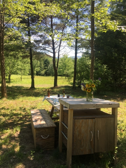 This Friday, June 29, 2018, photo shows a picnic table and cabinets at a Tentrr campsite on a 200-acre organic farm in Berlin, N.Y., near the Vermont border. The dining setup is standard equipment provided by Tentrr, along with a safari tent, Adirondack chairs and other gear. Like Airbnb or Uber for the great outdoors, Tentrr provides a platform for landowners to earn some cash by sharing secluded and scenic sites for camping. (AP Photo/Mary Esch)