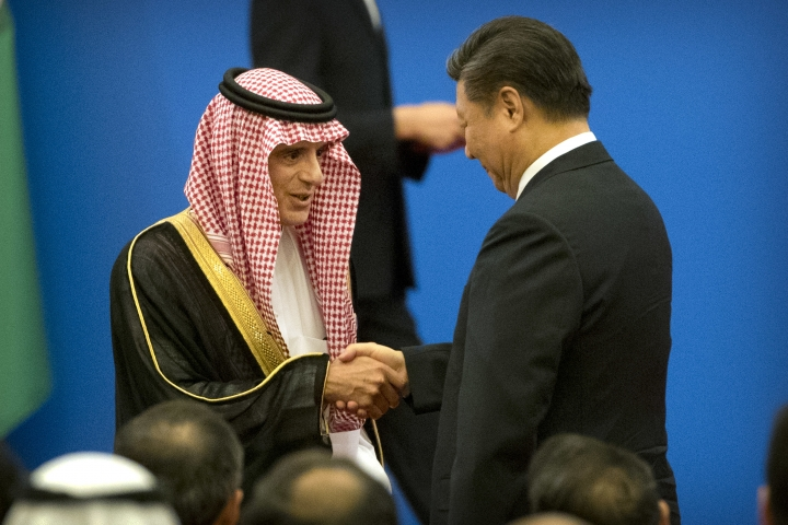 Saudi Arabia's Foreign Minister Adel al-Jubeir, left, shakes hands with Chinese President Xi Jinping after speaking during the opening session of the 8th Ministerial Meeting of the China-Arab States Cooperation Forum in Beijing, Tuesday, July 10, 2018. China's President Xi Jinping has pledged more than $23 billion in lines of credit, loans and humanitarian assistance to Arab countries in a major push for influence in the region. (AP Photo/Mark Schiefelbein)