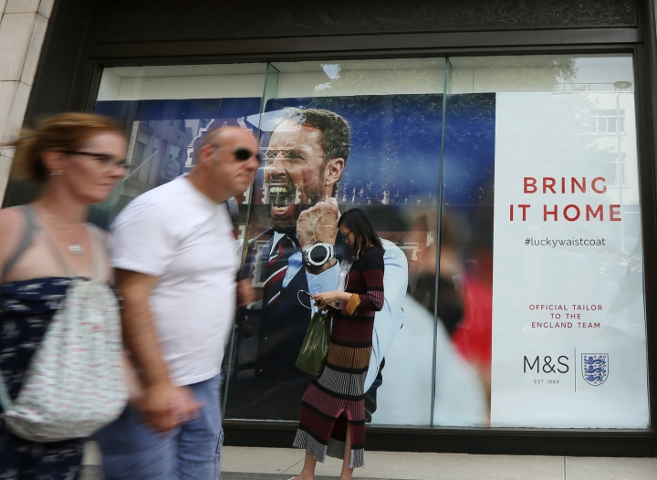 Shoppers pass the window of a Marks and Spencer store displays an image of England head coach Gareth Southgate in London, showing support for the England soccer team. The soft-spoken Southgate in a simple blue waistcoat seems to be uniting Britain amid dreams of victory in soccer's World Cup, with their next match against Croatia on upcoming Wednesday. (Robert Stevens/AP Photo)