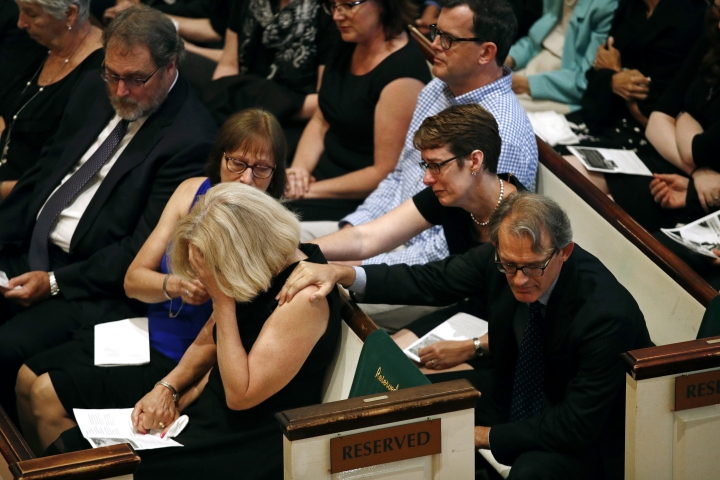 Andrea Chamblee, bottom left, widow of John McNamara, one of the journalists killed in the shooting at the Capital Gazette newspaper offices, is comforted during a memorial service for McNamara, Tuesday, July 10, 2018, in College Park, Md. (AP Photo/Patrick Semansky)