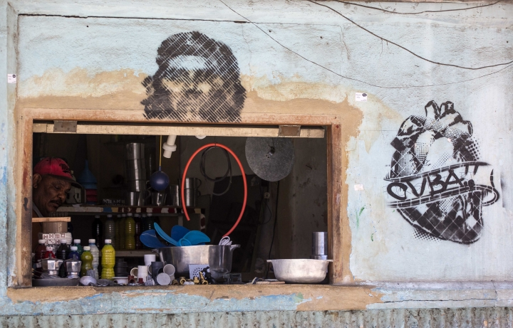 """A worker sits behind the window entrance of a privately licensed home appliance store, decorated with an Ernesto """"Che"""" Guevara drawing, in Havana, Cuba, Tuesday, July 10, 2018. The Cuban government will allow new restaurants, bed-and-breakfasts and transportation businesses by the end of the year 2018, reopening the most vibrant sectors of the private economy after freezing growth for more than a year. (AP Photo/Desmond Boylan)"""