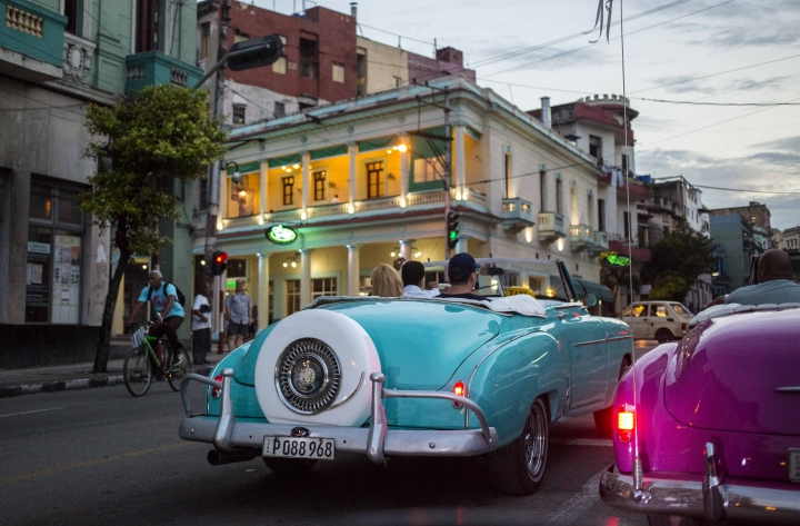 FILE - In this June 25, 2018 file photo, tourists ride classic American convertibles in Havana, Cuba. The Cuban government will allow new restaurants, bed-and-breakfasts and transportation businesses by the end of the year 2018, reopening the most vibrant sectors of the private economy after freezing growth for more than a year. (AP Photo/Desmond Boylan, File)