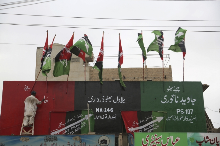 Pakistan artist writes slogans for Pakistan Peoples party ahead of general elections in Karachi, Pakistan, Tuesday, July 10, 2018. Pakistan's military announced on Tuesday that it would deploy more than 371,000 members of the country's security forces to polling stations to ensure free, fair and transparent national elections on July 25. (AP Photo/Shakil Adil)