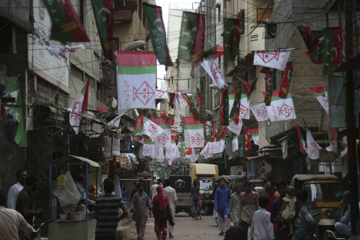 A street is decorated with posters of election candidates in Karachi, Pakistan, Tuesday, July 10, 2018. Pakistan's military announced on Tuesday that it would deploy more than 371,000 members of the country's security forces to polling stations to ensure free, fair and transparent national elections on July 25. (AP Photo/Shakil Adil)
