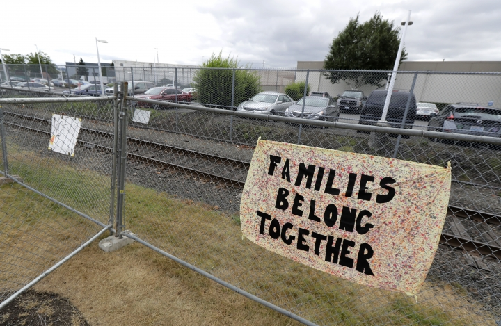 "A sign that reads ""Families belong Together"" hangs on a fence outside the Northwest Detention Center in Tacoma, Wash., Tuesday, July 10, 2018. The Trump administration rushed to meet a deadline Tuesday for reuniting dozens of youngsters forcibly separated from their families at the U.S.-Mexico border. (AP Photo/Ted S. Warren)"