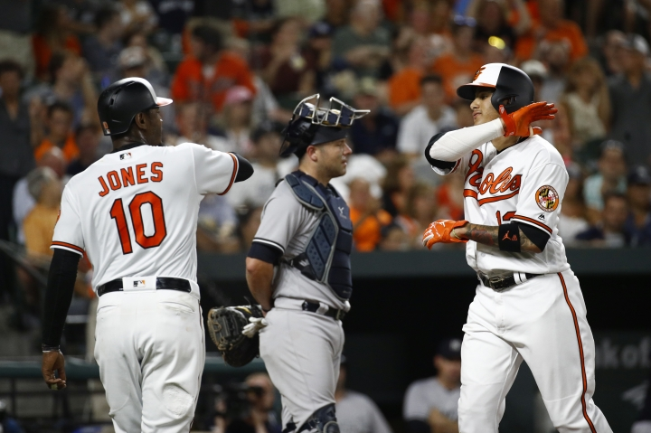 Baltimore Orioles' Manny Machado, right, greets teammate Adam Jones in front of New York Yankees catcher Austin Romine after batting Jones in on a two-run home run in the seventh inning of a baseball game, Tuesday, July 10, 2018, in Baltimore. (AP Photo/Patrick Semansky)