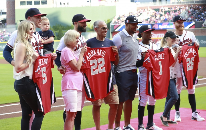 Atlanta Braves All-Stars, from left, Freddie Freeman with his wife, Chelsea, and son Charlie; Nick Markakis with his parents, Dennis and Mary Lou Markakis; Ozzie Albies with former Braves outfielder Andruw Jones, and Mike Foltynewicz with his wife, Brittany, and son Jett are presented their All-Star jerseys before the Braves played the Toronto Blue Jays in a baseball game Tuesday, July 10, 2018, in Atlanta. (Curtis Compton/Atlanta Journal-Constitution via AP)