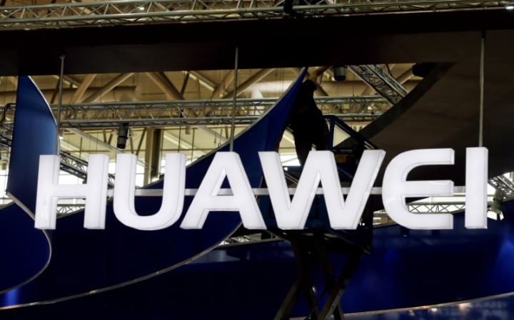 FILE PHOTO: A worker adjusts the logo at the stand of Huawei at the CeBIT trade fair in Hanover, in this file picture taken March 15, 2015. REUTERS/Morris Mac Matzen/File Photo
