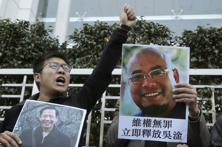 FILE - In this Dec. 27, 2017, file photo, pro-democracy activists hold pictures of Chinese activists Qin Yongmin, left, and Wu Gan outside the Chinese central government's liaison office in Hong Kong. China on Wednesday, July 11, 2018, has sentenced Qin, a veteran pro-democracy campaigner, to 13 years in prison on vaguely defined subversion charges, one day after releasing the widow of a Nobel Peace Prize laureate. (AP Photo/Kin Cheung, File)