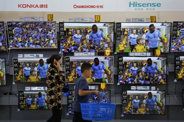 """A woman and a child pass Chinese brands of flat screen TVs on display at a hypermarket in Beijing, Wednesday, July 11, 2018. China's government has criticized the latest U.S. threat of a tariff hike as """"totally unacceptable"""" and vowed to retaliate in their escalating trade war. The Commerce Ministry on Wednesday gave no details, but Beijing responded to last week's U.S. tariff hike on $34 billion of imports from China by increasing its own duties on the same amount of American goods. (AP Photo/Andy Wong)"""