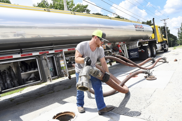FILE- In this Friday, June 29, 2018, file photo, Colin Hinshaw with Hilco Transport INC. in Greensboro, fills the fuel storage tanks at the Pick N Go gas station in High Point, N.C. On Wednesday, July 11, the Labor Department reports on U.S. producer price inflation for June. (Laura Greene/The High Point Enterprise via AP, File)