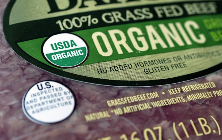 """In this Monday, July 9, 2018 photo a """"USDA Organic"""" label is printed on the label of a pound of ground beef, in Walpole, Mass. The USDA Organic label generally signifies a product is made without synthetic pesticides and fertilizers, and that animals are raised according to certain standards. But disputes over the rules and reports of fraud may have some questioning whether the seal is worth the price. (AP Photo/Steven Senne)"""