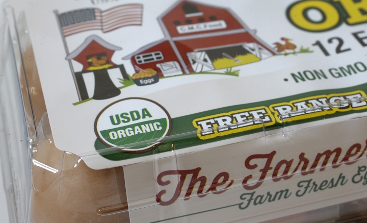 """In this Monday, July 9, 2018 photo a """"USDA Organic"""" label is printed on the label of a carton of a dozen eggs, in Walpole, Mass. The USDA Organic label generally signifies a product is made without synthetic pesticides and fertilizers, and that animals are raised according to certain standards. But disputes over the rules and reports of fraud may have some questioning whether the seal is worth the price. (AP Photo/Steven Senne)"""