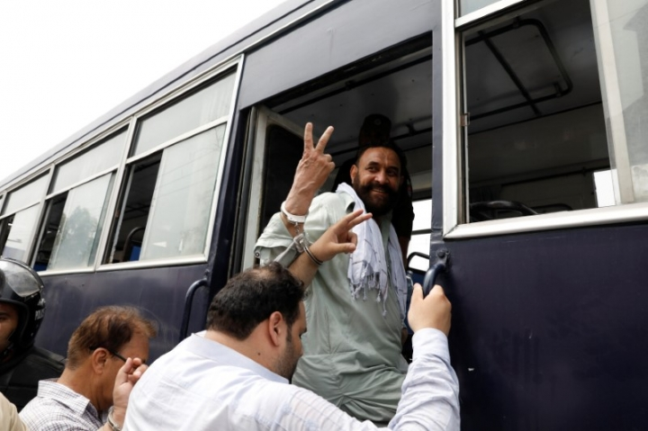 FILE PHOTO: The supporters Pakistan Muslim League-Nawaz (PML-N) who were arrested after holding a rally to obstruct the arrest of Mohammad Safdar, the son-in-law of ousted Prime Minister Nawaz Sharif, gesture from a prison van after they appeared before the district court in Rawalpindi, Pakistan July 11, 2018. REUTERS/Faisal Mahmood