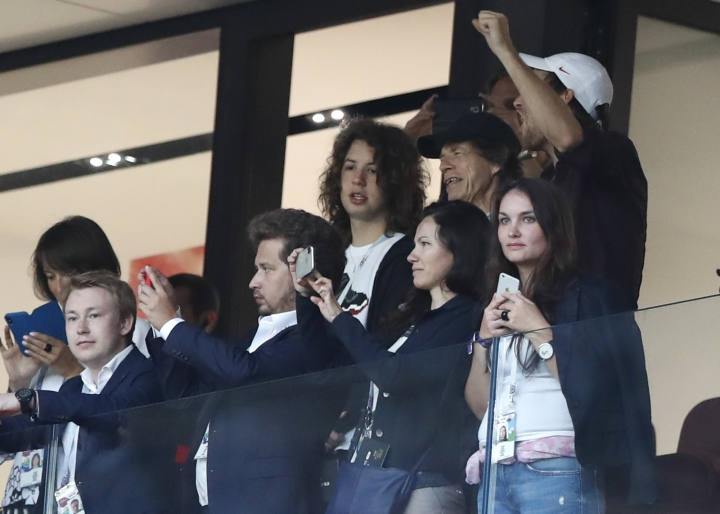 Singer Mick Jagger of the Rolling Stones, in black baseball hat, smiles during the semifinal match between Croatia and England at the 2018 soccer World Cup in the Luzhniki Stadium in, Moscow, Russia, Wednesday, July 11, 2018. (AP Photo/Alastair Grant)