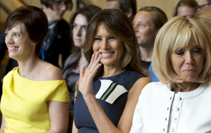 U.S. first lady Melania Trump, center, waves as she prepares to listen to a concert at the Queen Elisabeth Music Chapel in Waterloo, Belgium, during a spouses program on the sidelines of the NATO summit on Wednesday, July 11, 2018. At right is Brigitte Macron, the wife of French President Emmanuel Macron and at left is Amelie Derbaudrenghien, the partner of Belgian Prime Minister Charles Michel.(AP Photo/Virginia Mayo)