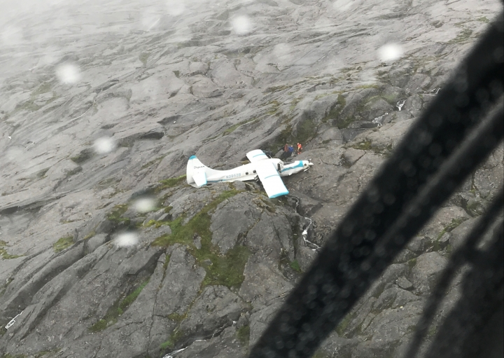 In this July 10, 2018 photo, Coast Guard Air Station Sitka MH-60 Jayhawk helicopter crews rescue people after a float plane crashed southwest of Ketchikan, Alaska, on Prince of Wales Island. All the people aboard a plane that crashed Tuesday have been rescued in mountainous terrain, officials said. (U.S. Coast Guard via AP)