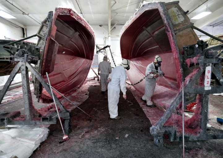Workers apply fiberglass to the resin frame of a boat at Regal Marine Industries in Orlando, Fla., Wednesday, July 11, 2018. Some U.S. manufacturers are feeling the impact of tariffs of up to 25 percent that the Trump administration has imposed on thousands of products imported from China, Europe, Mexico, Canada, India and Russia, and of retaliatory tariffs that countries have put on U.S. exports. Among the products the U.S. has targeted are aluminum, steel and goods made from those metals, vehicles and their components and computer parts. The retaliation has hit U.S. makers of food and farm products, alcoholic beverages and boats and other vehicles. (AP Photo/John Raoux)