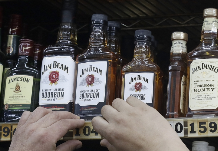 """This July 9, 2018, photo shows a man adjusting prices under bottles of Jim Beam bourbon whiskey displayed at Rossi's Deli in San Francisco. China's government vowed Wednesday, July 11, to take """"firm and forceful measures"""" as the U.S. threatened to expand tariffs to thousands of Chinese imports. After the U.S. imposed 25 percent tariffs on $34 billion worth of Chinese goods, China retaliated by imposing tariffs on the same amount of U.S. products including whiskey. (AP Photo/Jeff Chiu)"""