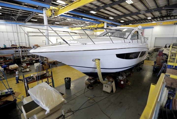 Workers inside this boat apply finishing details at Regal Marine Industries in Orlando, Fla., Wednesday, July 11, 2018. Some U.S. manufacturers are feeling the impact of tariffs of up to 25 percent that the Trump administration has imposed on thousands of products imported from China, Europe, Mexico, Canada, India and Russia, and of retaliatory tariffs that countries have put on U.S. exports. Among the products the U.S. has targeted are aluminum, steel and goods made from those metals, vehicles and their components and computer parts. The retaliation has hit U.S. makers of food and farm products, alcoholic beverages and boats and other vehicles. (AP Photo/John Raoux)