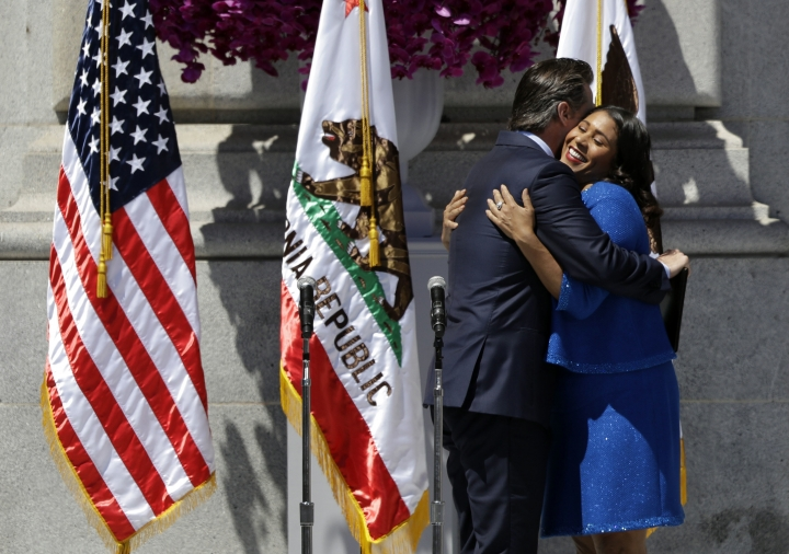 California Lt. Gov. Gavin Newsom, left, hugs London Breed before swearing her in as San Francisco's new mayor Wednesday, July 11, 2018, outside City Hall in San Francisco. The 43-year-old Breed becomes the city's first African-American female mayor and she inherits a San Francisco battling homelessness, open drug use and unbearably high housing costs. (AP Photo/Marcio Jose Sanchez)