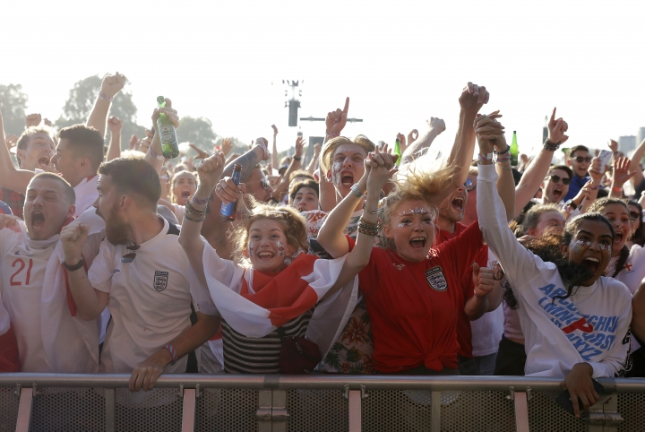 England soccer fans celebrates England's first goal as they watch a live broadcast on a big screen of the semifinal match between Croatia and England at the 2018 soccer World Cup, in Hyde Park, London, Wednesday, July 11, 2018. (AP Photo/Matt Dunham)