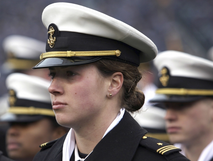 FILE - In this Dec. 14, 2013 file photo, Navy women's soccer goalkeeper Elizabeth Hoerner stands in formation before the start of the Army Navy NCAA college football game at Lincoln Financial Field in Philadelphia. The U.S. Navy said Tuesday, July 10, 2018, it will let women sailors sport ponytails and other longer hairstyles, reversing a policy that long forbade females from letting their hair down. (AP Photo/Jacqueline Larma, File)