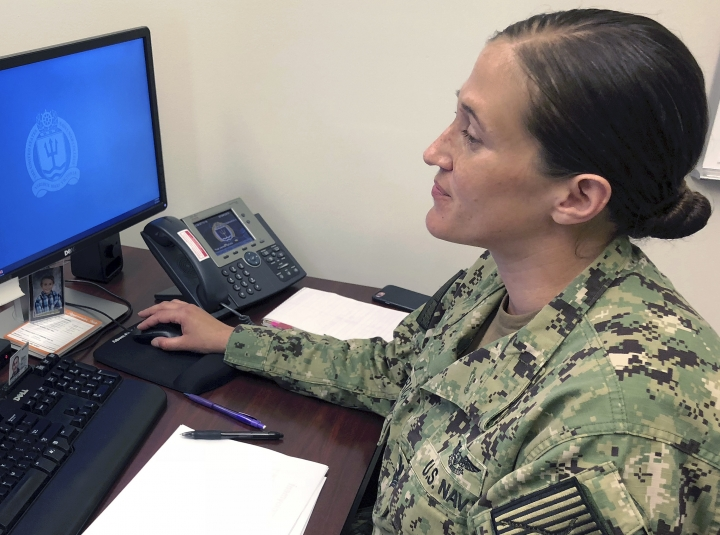 U.S. Navy Legalman First Class Tamatha Schulmerich works at her desk at the Naval War College, Wednesday, July 11, 2018, in Newport, R.I. The Navy said Tuesday it will let women sailors sport ponytails and other longer hairstyles, reversing a policy that long forbade females from letting their hair down. (AP Photo/Jennifer McDermott)