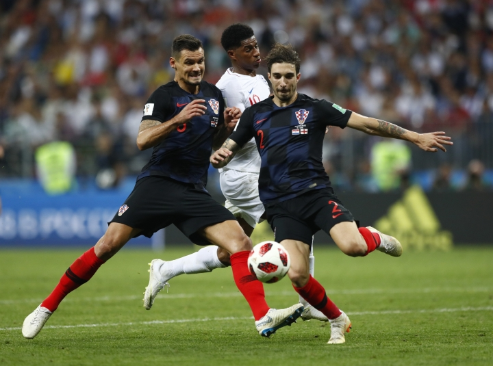 England's Raheem Sterling, center, is stopped by Croatia's Dejan Lovren, left, and Croatia's Sime Vrsaljko during the semifinal match between Croatia and England at the 2018 soccer World Cup in the Luzhniki Stadium in Moscow, Russia, Wednesday, July 11, 2018. (AP Photo/Matthias Schrader)