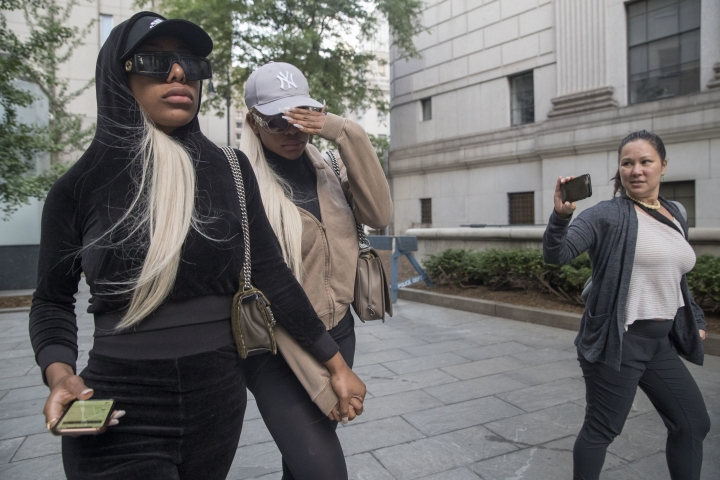 "Shannade Clermont, center, and her twin sister Shannon are followed by a reporter as they leave Federal court in New York after her arraignment, Wednesday, July 11, 2018. Shannade Clermont, a former cast member of the television reality series ""Bad Girls Club,"" was arrested on charges alleging she stole debit card information from a man who died shortly after a date with her. (AP Photo/Mary Altaffer)"
