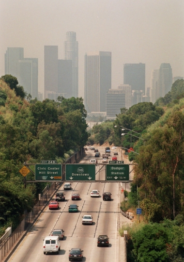 FILE - In this July 1998 file photo, traffic drives toward downtown Los Angeles on the 110 freeway as a curtain of smog shrouds the skyline. California greenhouse gas emissions fell below 1990 levels, meeting an early target years ahead of schedule and putting the state well on its way toward reaching long-term goals to fight climate change, officials said Wednesday, July 11, 2018. (AP Photo/Nick Ut, File)