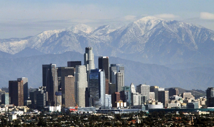 FIE - In this Dec. 31, 2014, file photo, the snow-capped San Gabriel Mountains provide a backdrop to the downtown Los Angeles skyline as seen from Kenneth Hahn State Recreation Area in Baldwin Hills. California greenhouse gas emissions fell below 1990 levels, meeting an early target years ahead of schedule and putting the state well on its way toward reaching long-term goals to fight climate change, officials said Wednesday, July 11, 2018. (AP Photo/Nick Ut, File)