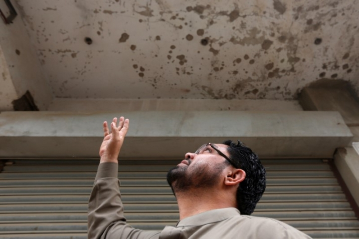 Zakir Hanif, an activist of Awami National Party, points to the ceiling of his pharmacy store which was bombed by the Tehreek-e-Taliban Pakistan (TTP), in Karachi, Pakistan January 25, 2017. REUTERS/Akhtar Soomro