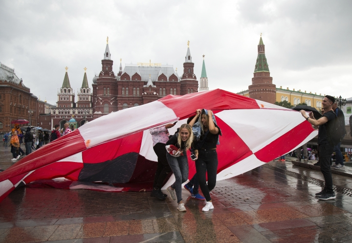 Soccer fans use a giant Croatian national flag as a shelter during the rain at Manezh Square near Red Square ahead of the semifinal soccer match between Croatia and England during the 2018 soccer World Cup at the Luzhniki stadium in Moscow, Russia, Wednesday, July 11, 2018. (AP Photo/Alexander Zemlianichenko)