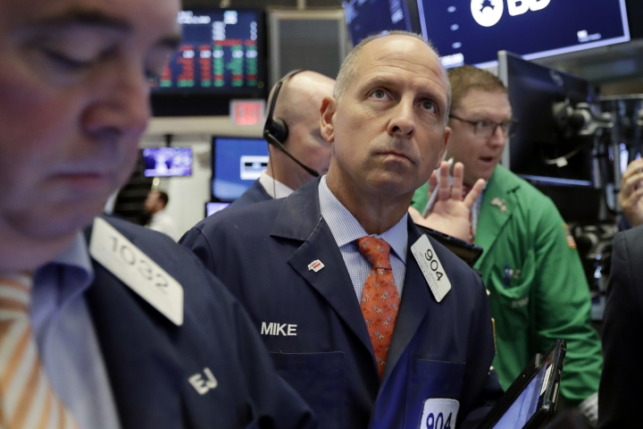 Trader Michael Urkonis, center, works on the floor of the New York Stock Exchange, Wednesday, July 11, 2018. Stocks are opening lower on Wall Street, following declines in Europe and Asia, after Washington threatened to expand tariffs on Beijing and China said it would retaliate. (AP Photo/Richard Drew)