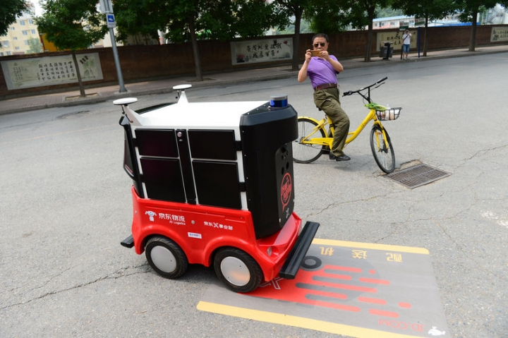 A man riding an Ofo shared bicycle takes pictures of a JD.com delivery robot on a road in Beijing, China June 18, 2018. REUTERS/Stringer