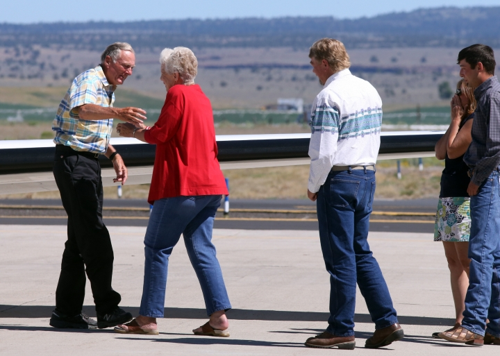 Rancher Dwight Hammond Jr. is embraced by his wife Susie Hammond after arriving by private jet at the Burns Municipal Airport, Wednesday, July 11, 2018, in Burns, Ore. Hammond and his son Steven, convicted of intentionally setting fires on public land in Oregon, were pardoned by President Donald Trump on Tuesday, July 10.( Beth Nakamura/The Oregonian via AP)