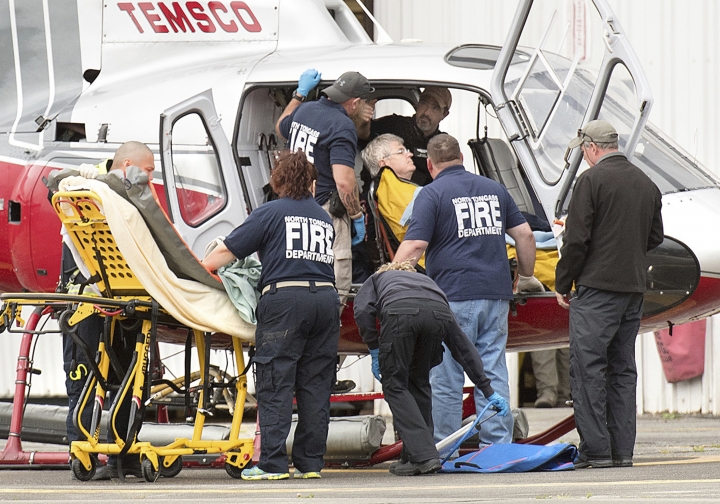 Emergency responders assist a passenger in Ketchikan, Alaska, Tuesday, July 10, 2018, after the crash of a Taquan Air float plane on Prince of Wales Island's Mt. Jumbo. The chartered Taquan Air flight plane crashed Tuesday on a rocky mountainside near Ketchikan. Everyone survived and were rescued hours later by the U.S. Coast Guard. (Dustin Safranek/The Ketchikan Daily News via AP)