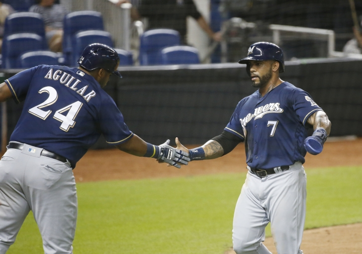 Milwaukee Brewers' Jesus Aguilar (24) congratulates Eric Thames (7) after Thames scored on a single by Christian Yelich during the third inning of a baseball game against the Miami Marlins, Wednesday, July 11, 2018, in Miami. (AP Photo/Wilfredo Lee)