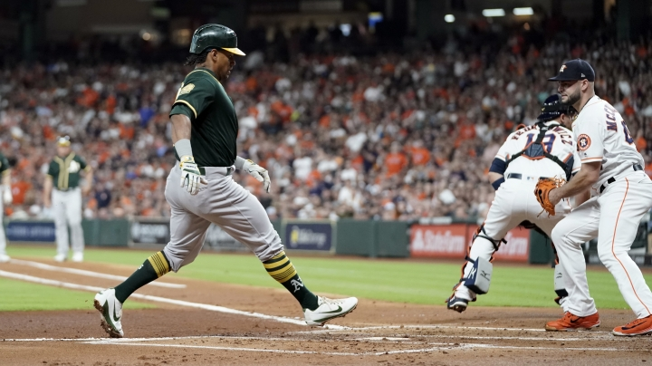 Oakland Athletics' Khris Davis, left, scores as Houston Astros starting pitcher Lance McCullers Jr., right, covers home plate during the first inning of a baseball game Wednesday, July 11, 2018, in Houston. (AP Photo/David J. Phillip)