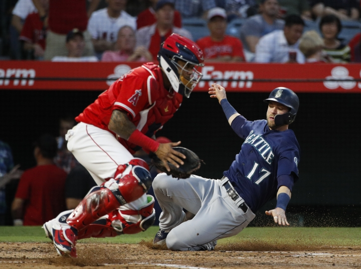 Seattle Mariners' Mitch Haniger, right, slides to score on a single by Nelson Cruz as Los Angeles Angels catcher Martin Maldonado waits for the throw during the fourth inning of a baseball game, Wednesday, July 11, 2018, in Anaheim, Calif. (AP Photo/Jae C. Hong)