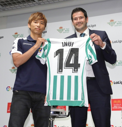 Japan's Takashi Inui, left, poses with his Real Betis' shirt as he received from the team's Business General Manager Ramon Alarcon, at the Spanish embassy in Tokyo Thursday, July 12, 2018. Inui has signed a contract with the Seville-based club until 2021, after he spent three seasons at Betis' La Liga rivals Eibar. (Kyodo News via AP)